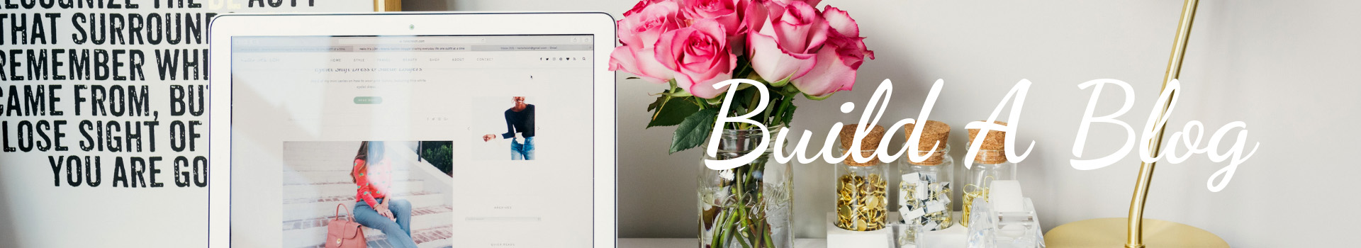 Blog header of a laptop, poster and floral arrangement on a desktop for the Build a Blog page