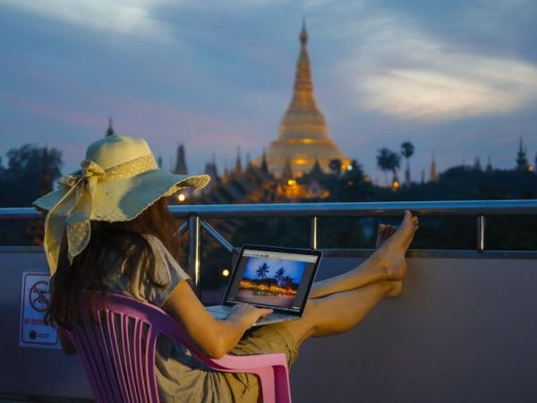 Lady sitting on a patio with her laptop on her lap overlooking the Shwedagon-Paya pagoda in Yangon, Burma.